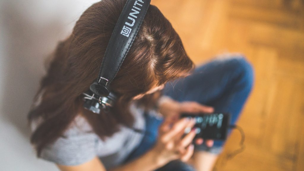 Woman with headphones and smartphone listening to media
